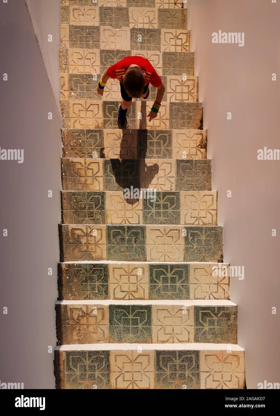 Un joven en una camiseta de la selección nacional de fútbol española, la escalada de azulejos estilo morisco pasos en Nerja. Costa del Sol, Málaga, Andalucía, España Foto de stock