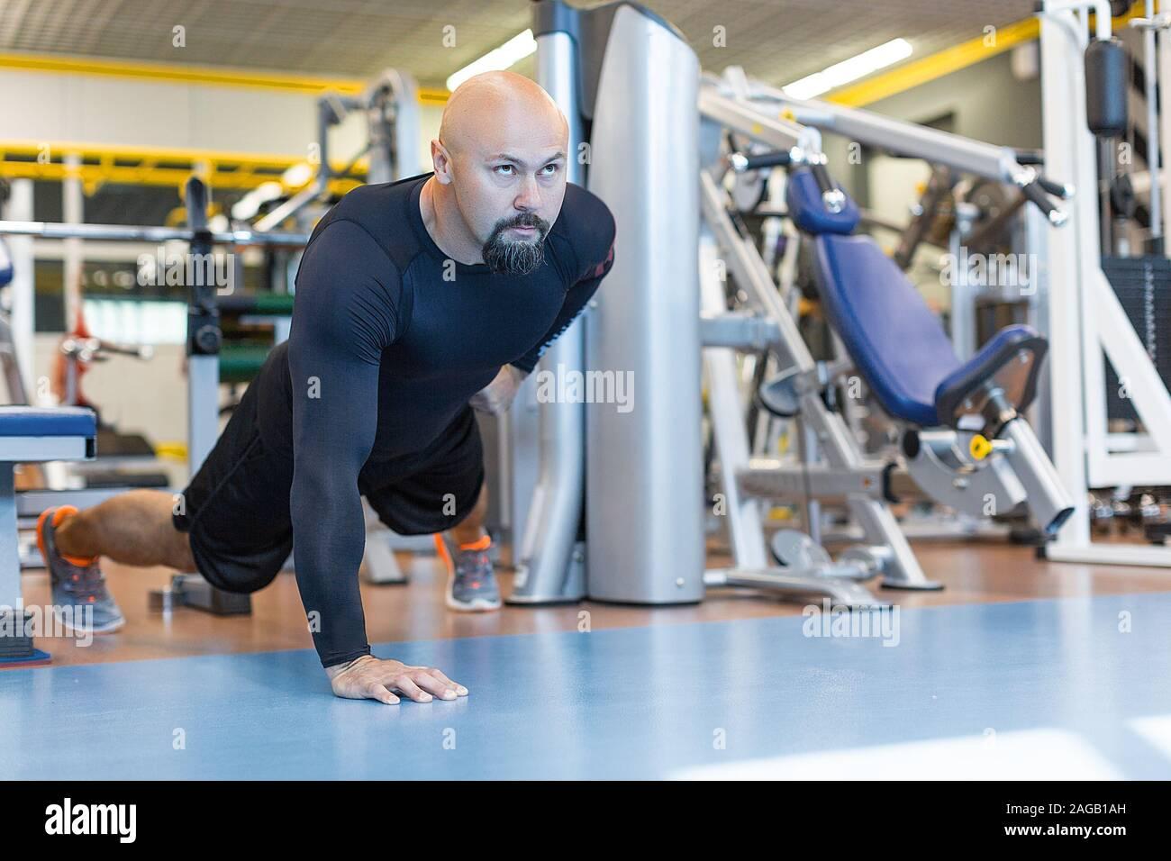 Hombre Barbado brutal haciendo flexiones con una mano de ejercicio en el gimnasio. Healty concepto de estilo de vida Foto de stock