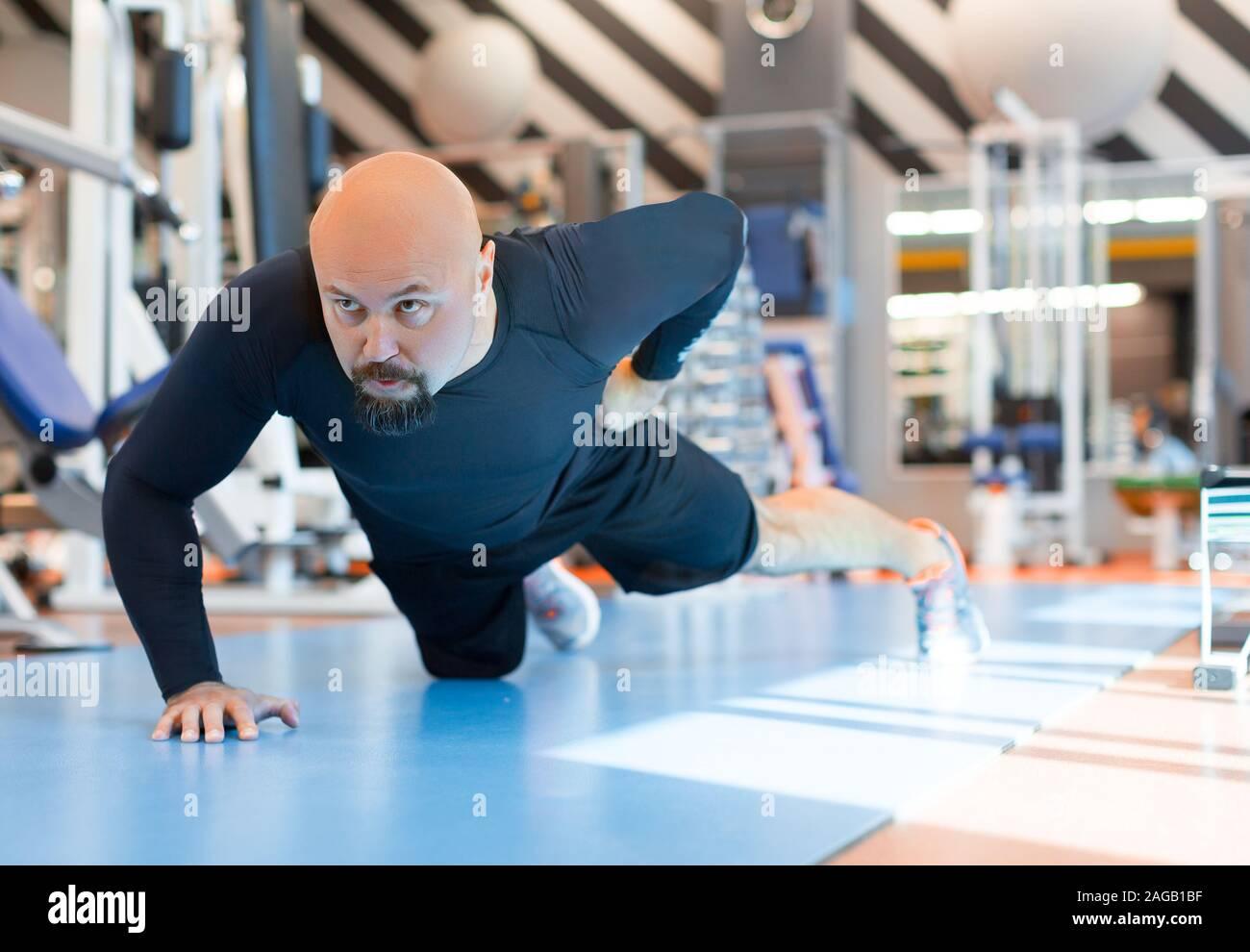 Hombre Barbado brutal haciendo flexiones con una mano de ejercicio en el gimnasio. Cierre vertical. Healty concepto de estilo de vida Foto de stock