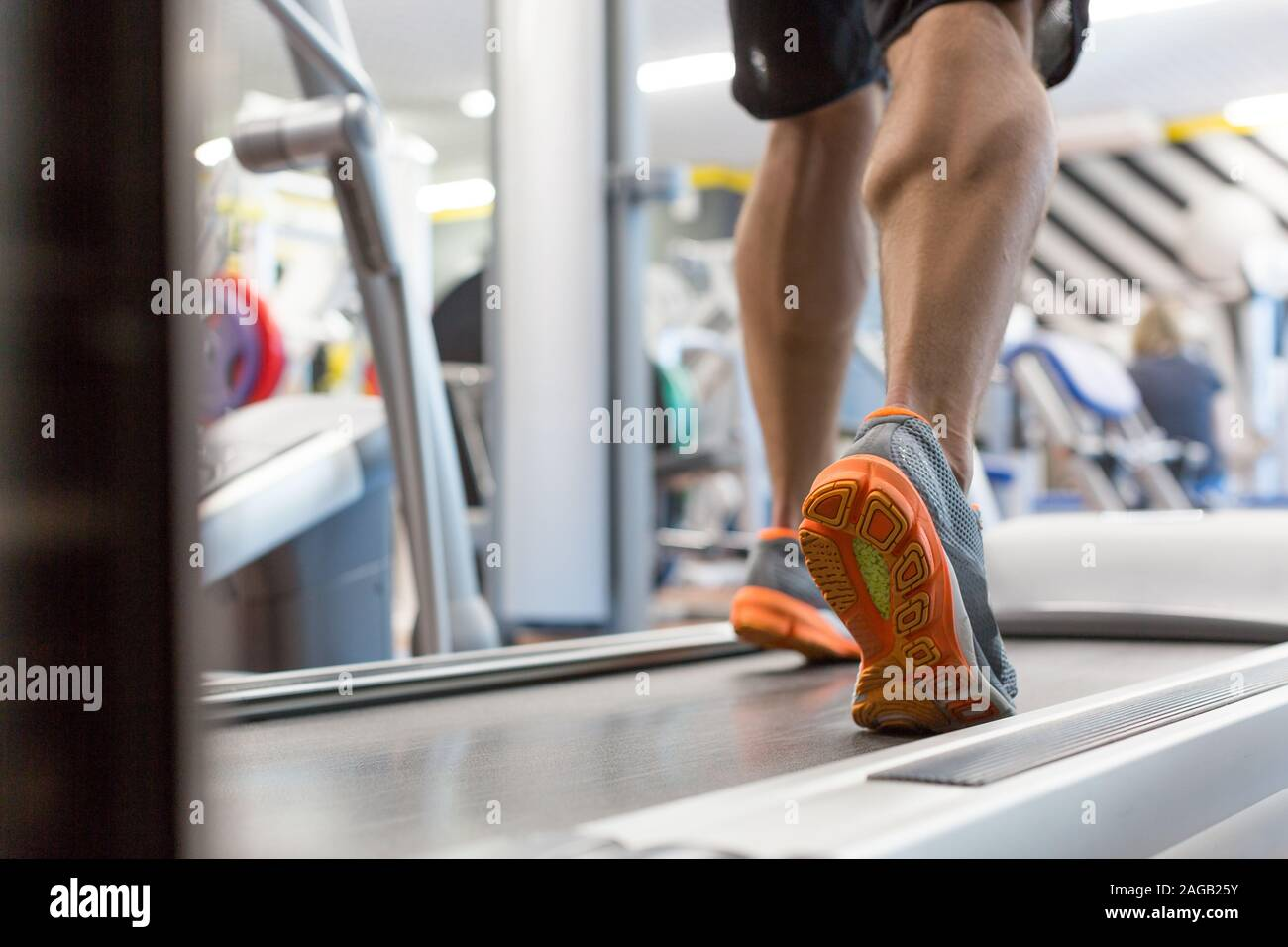 Cierre muscular masculina pies en zapatillas corriendo en la caminadora en el gimnasio. Fitness, Entrenamiento y concepto de estilo de vida saludable. Foto de stock