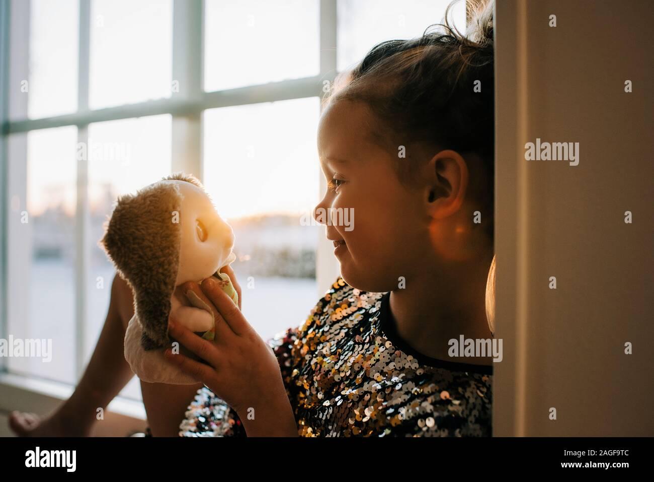 Joven mirando fijamente a su juguete en casa al atardecer Foto de stock