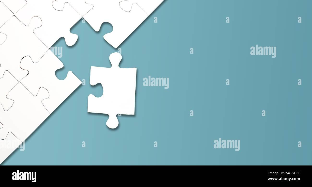 Vista superior del rompecabezas con una pieza izquierda sobre fondo azul, completar una tarea o resolver un problema de concepto Foto de stock