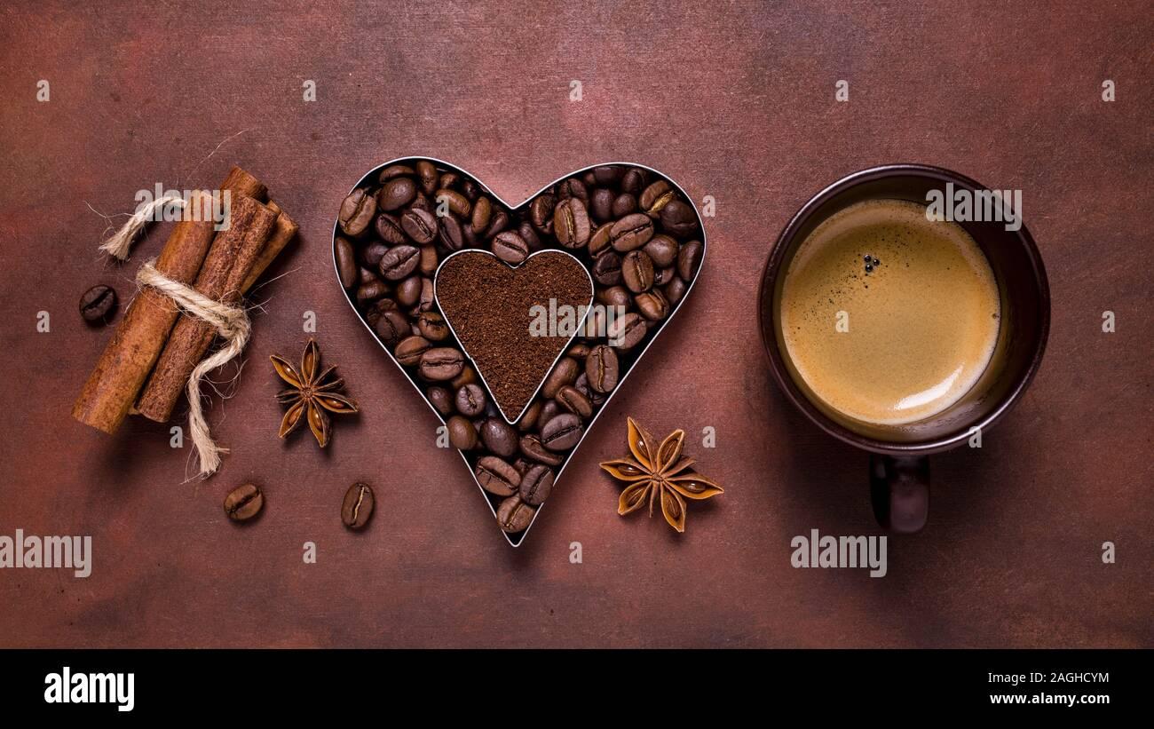 Composición con una taza de café, y la silueta en forma de corazón con los granos de café y café molido. Foto de stock