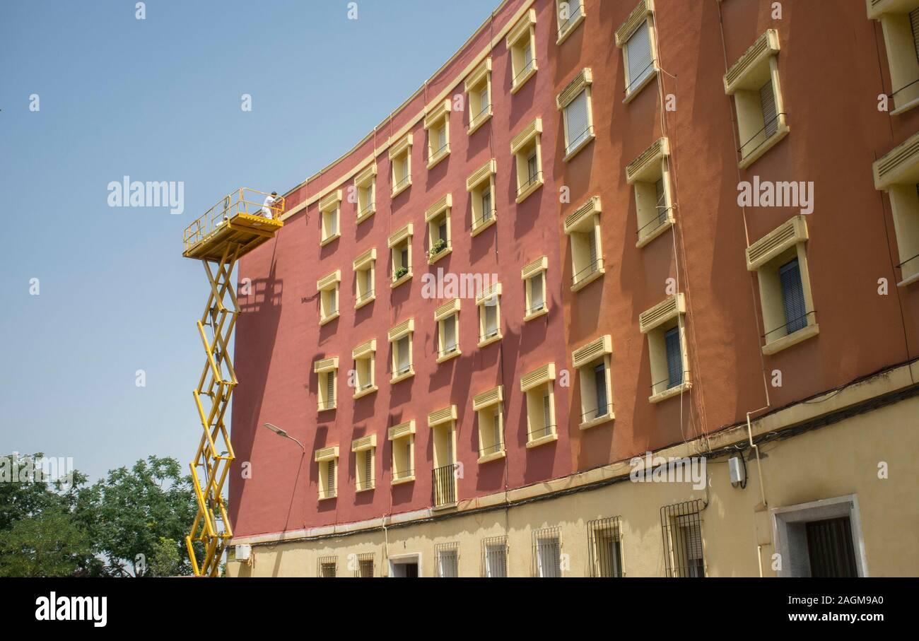 Pintor trabajando sobre la plataforma elevadora de tijera. Fondo urbano sobre cielo azul Foto de stock