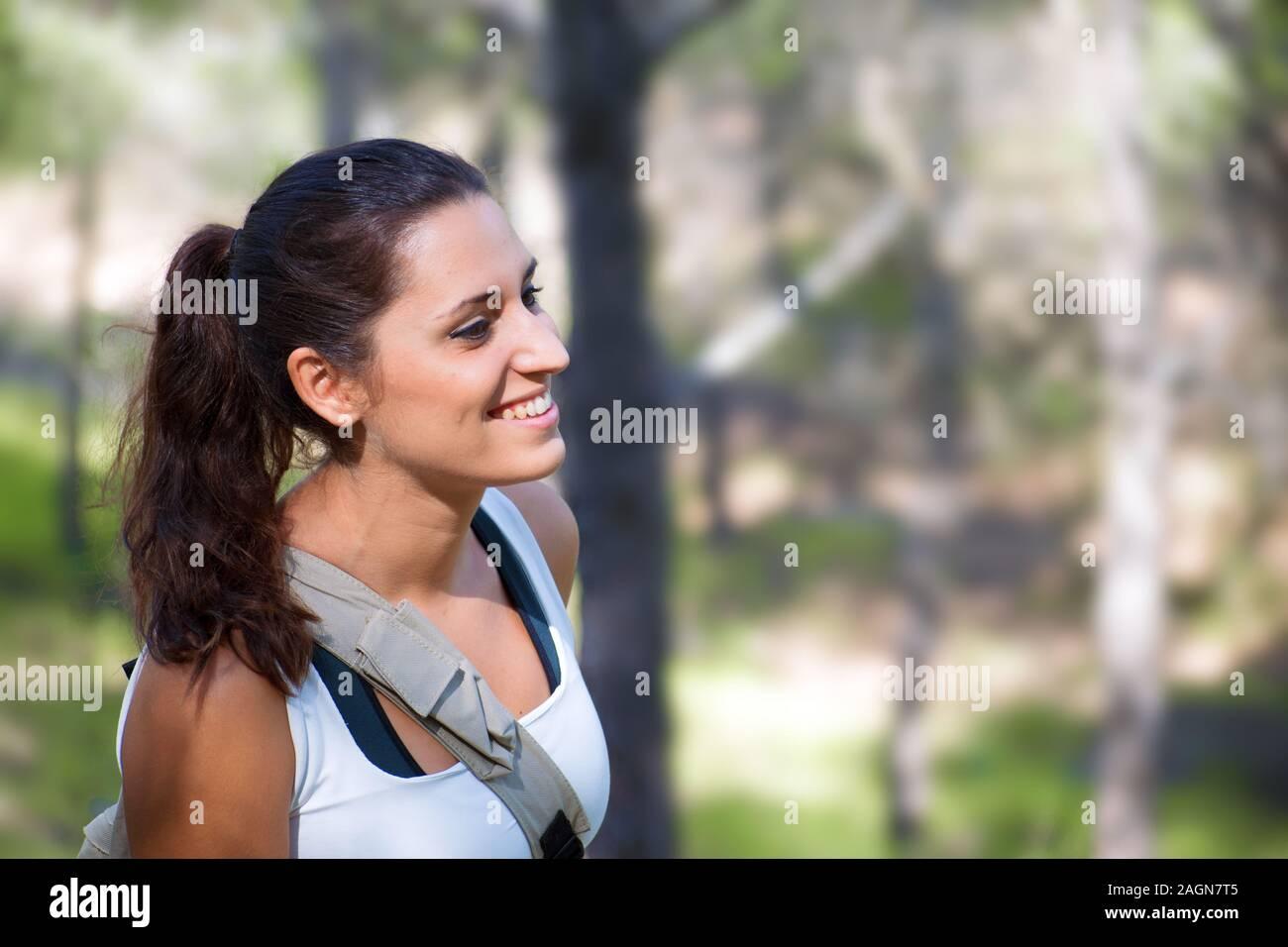 Mujer sonriente retrato vista lateral. Los jóvenes caucásicos chica española contra campos de agricultura. La libertad en la naturaleza. Foto de stock