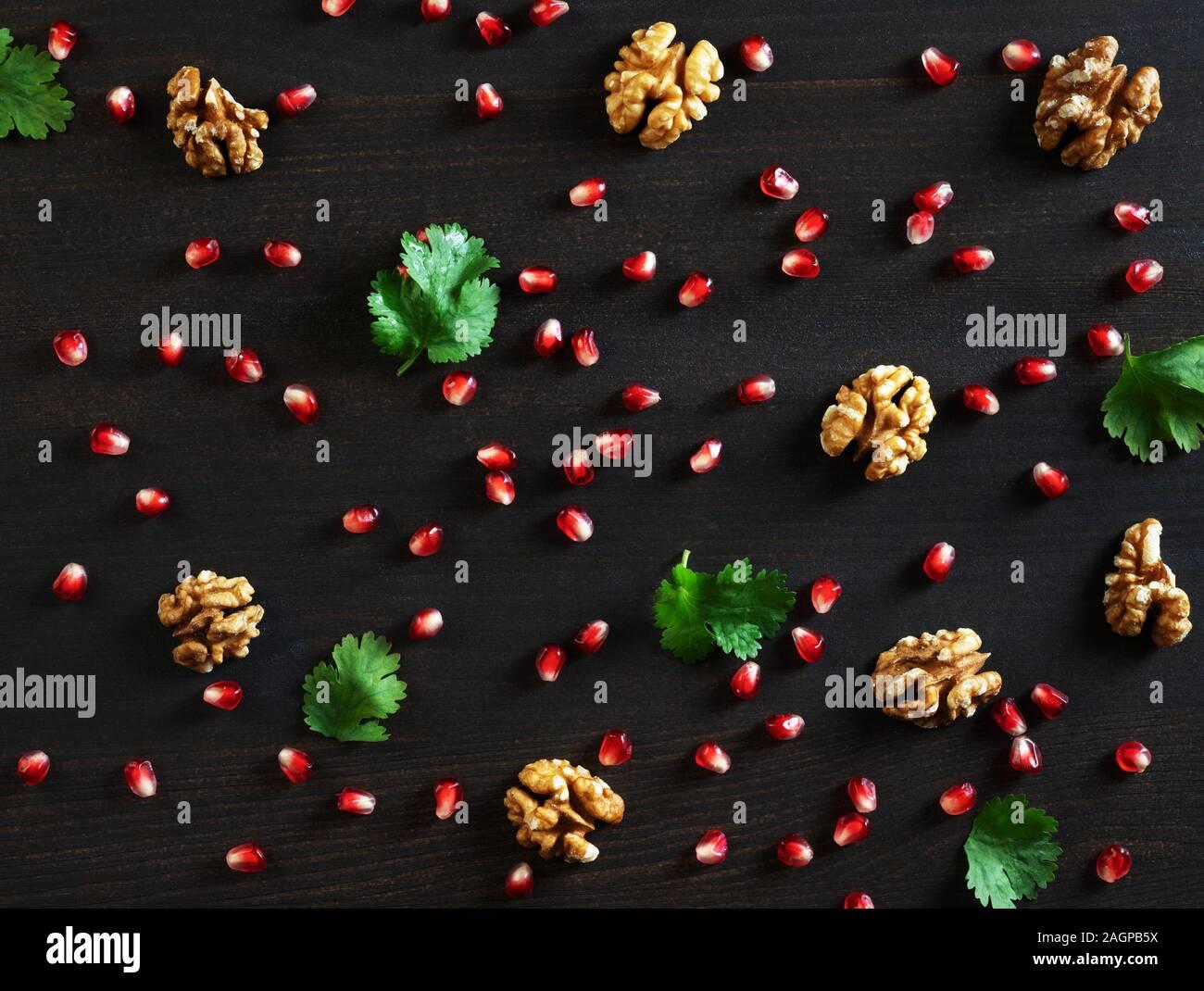 Fondo de alimentos. Semillas de Granada, nueces y cilantro sobre un fondo de madera oscura. Patrón alimentario. Sentar planas, vista superior. Foto de stock