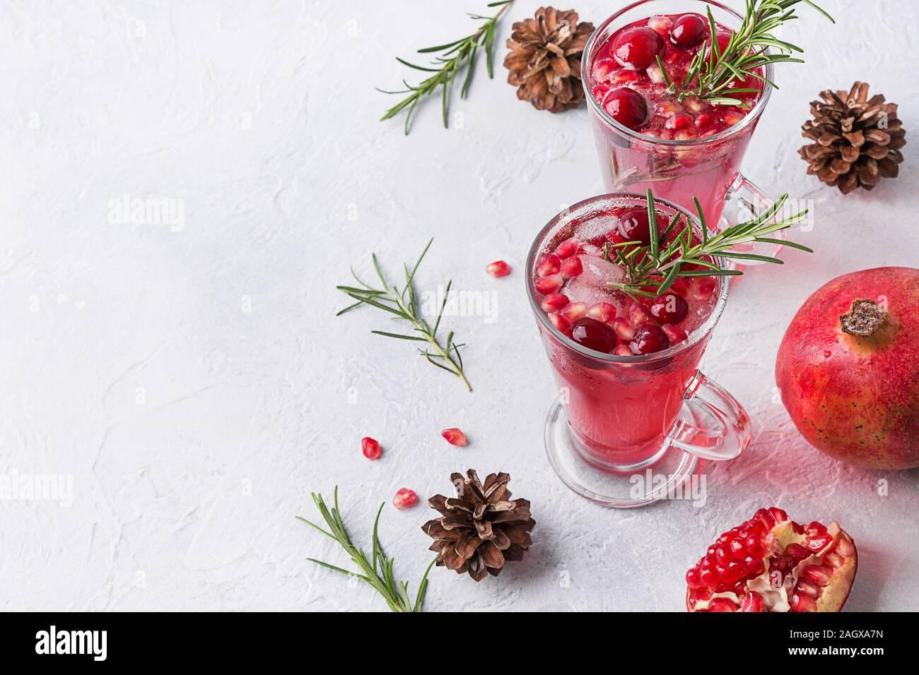 Dos copa de granada vacaciones de Navidad cóctel con romero, arándano, vino espumoso en el cuadro blanco. Bebida de Navidad. Espacio para el texto. Foto de stock