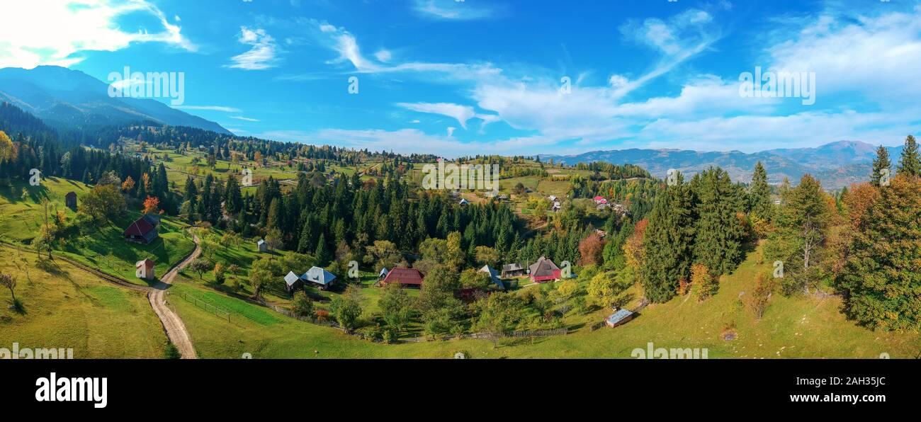 Vistas panorámicas aéreas de una región rural con granjas, campos y la cordillera de los Cárpatos en el fondo. Borsa, Maramures, Rumania. Foto de stock