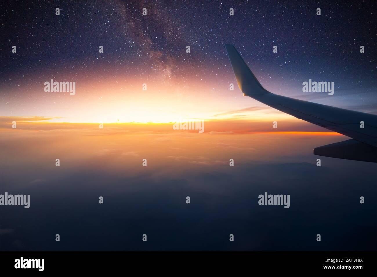 Avión está volando en la noche. El espacio de la Vía Láctea vista desde la ventana de avión. Claro oscuro cielo estrellado. Foto de stock