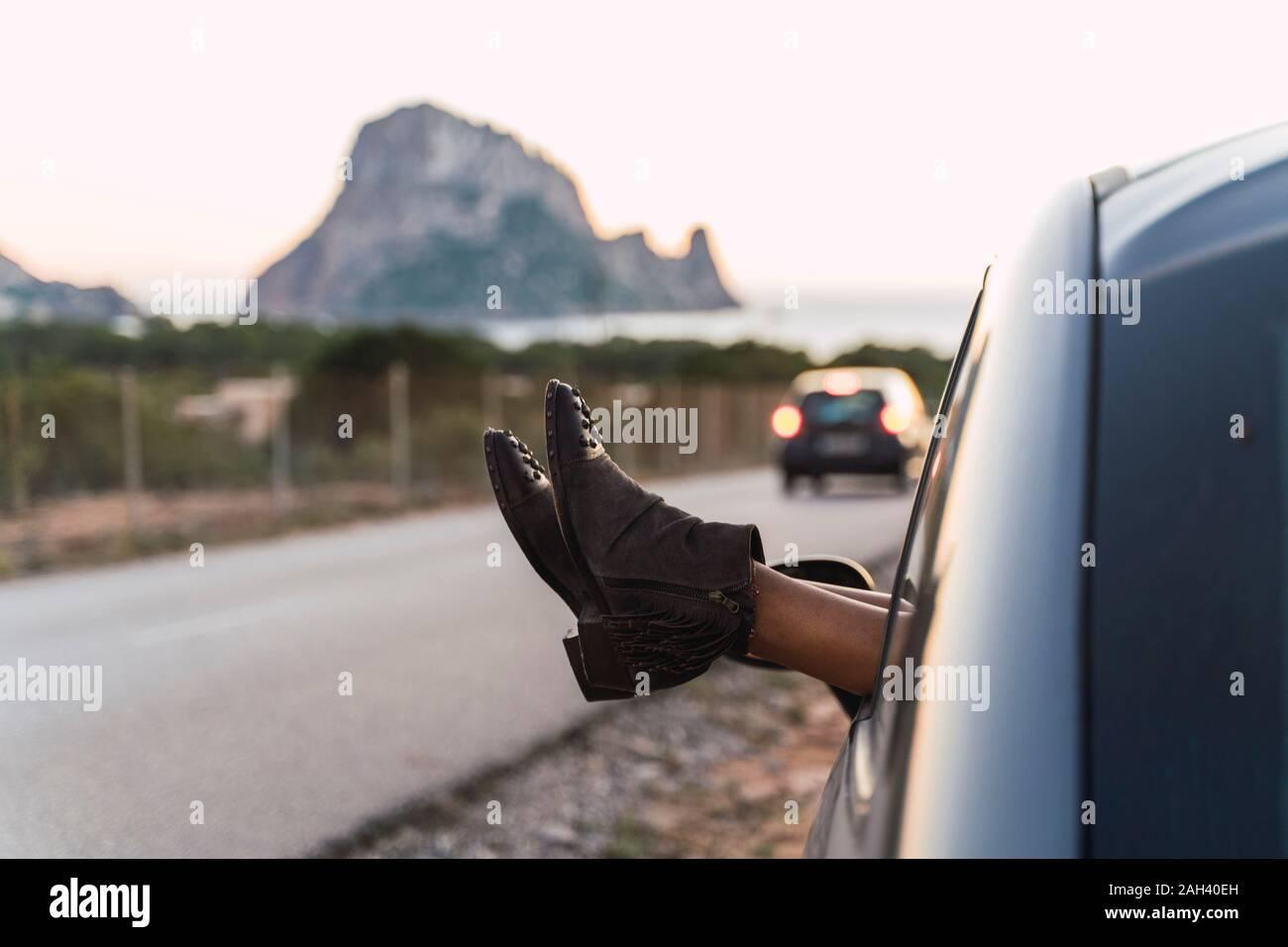Mujer joven durante el viaje por carretera, inclinándose hacia los ...