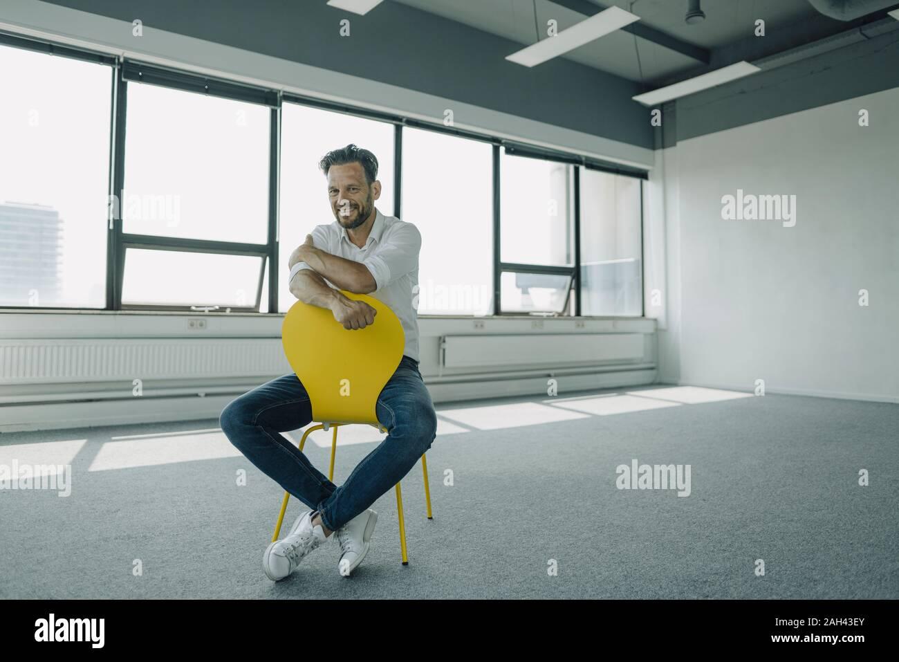 Retrato de confianza empresario maduro sentado en amarillo en silla de oficina vacía Foto de stock