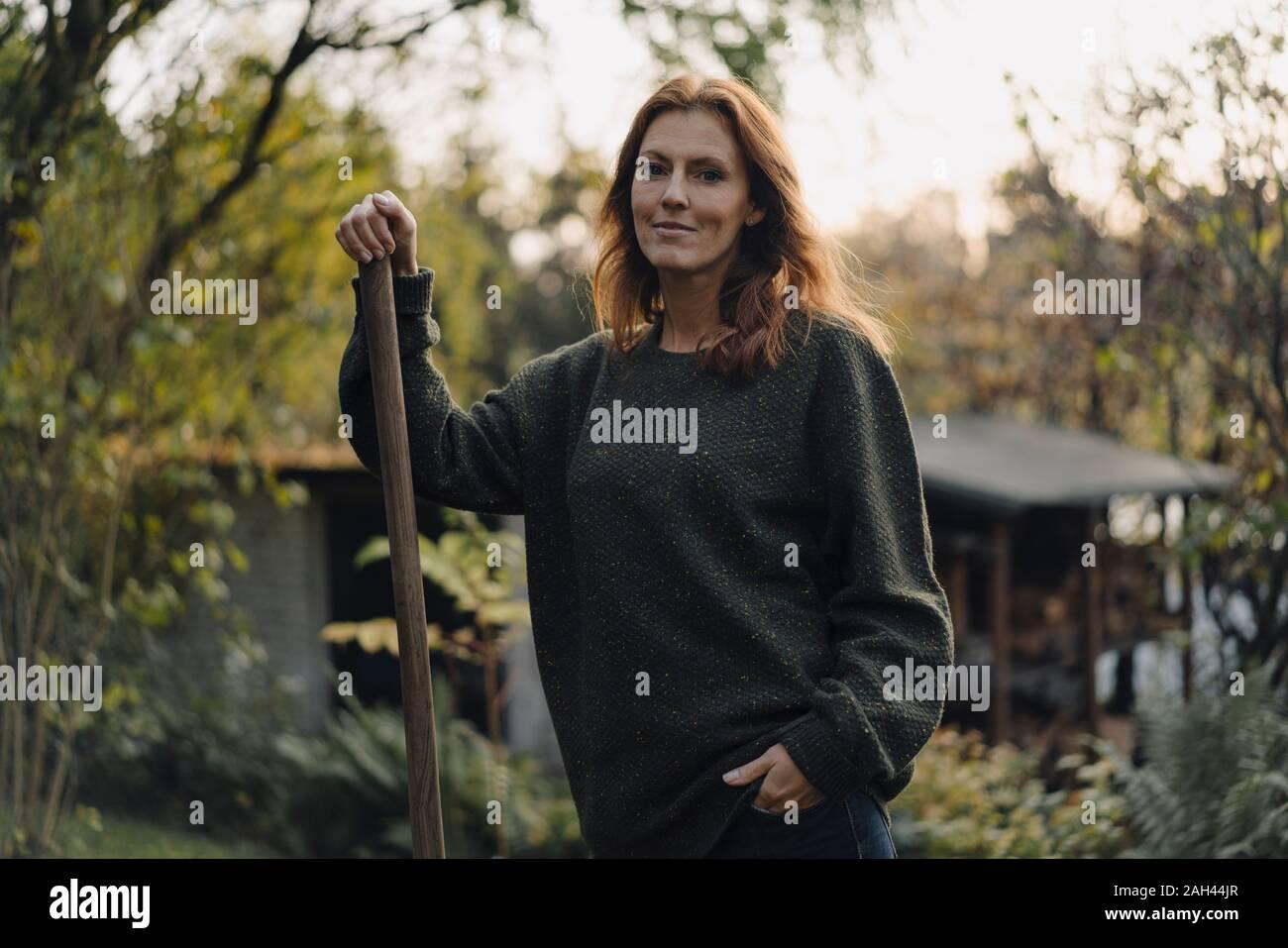 Mujer trabajando en su jardín, sosteniendo la pala Foto de stock