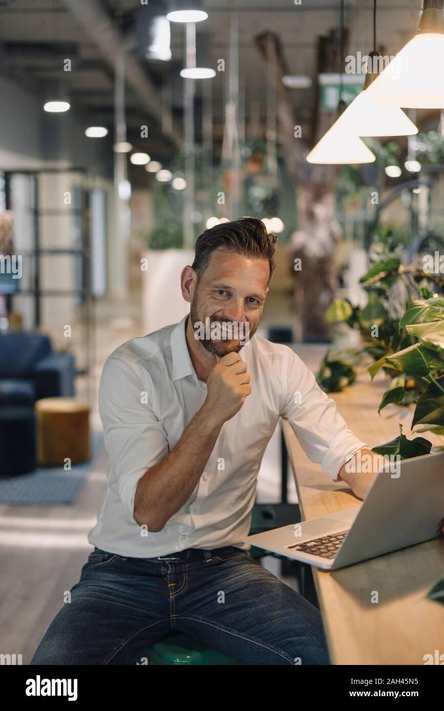 Retrato de sonriente empresario maduros usando el portátil en el salón moderno de oficina Foto de stock