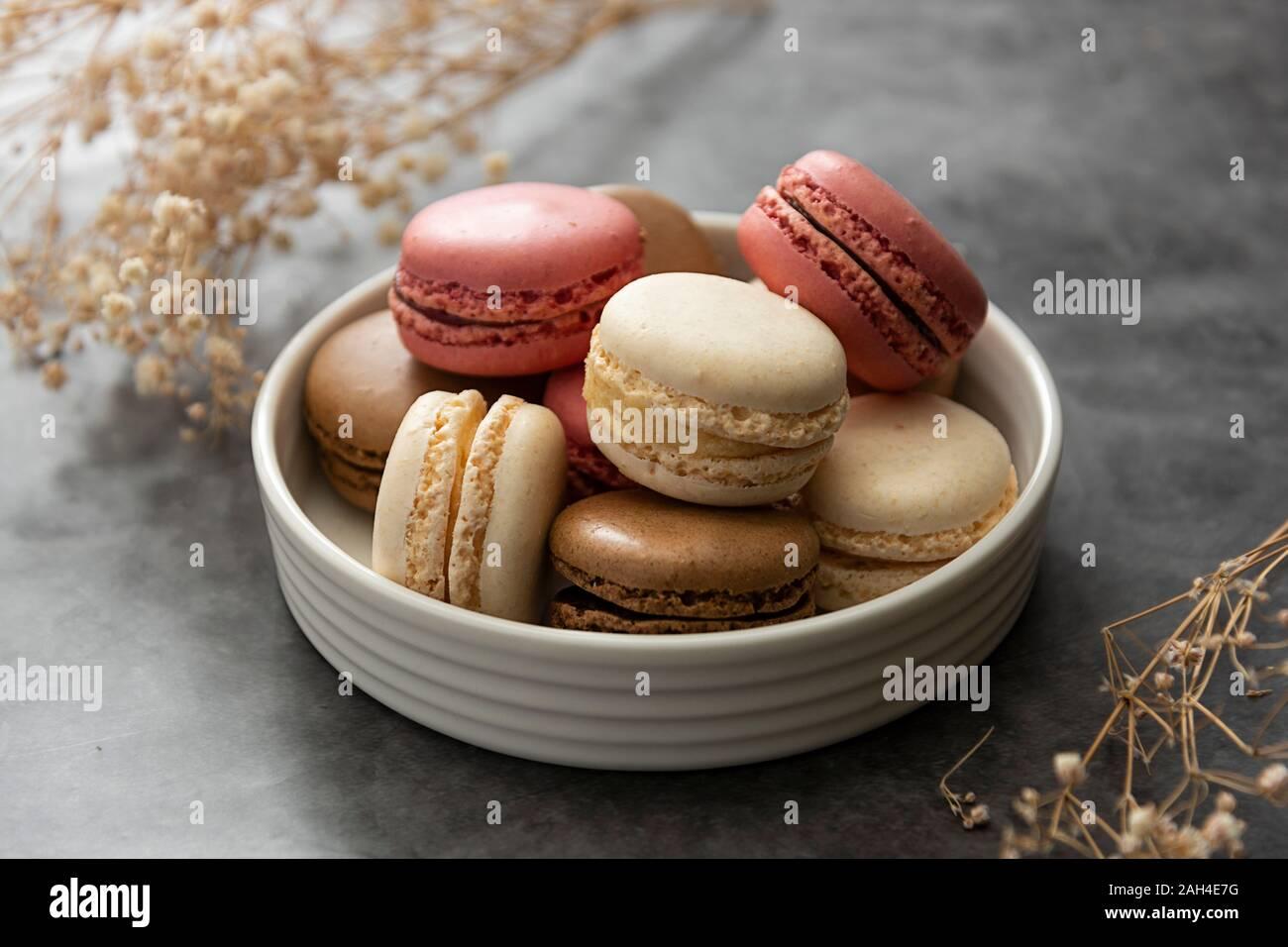 Francés macaron tartas en una placa de cerca. Crema, marrón, rosado, macarons con espacio de copia. Foto de stock