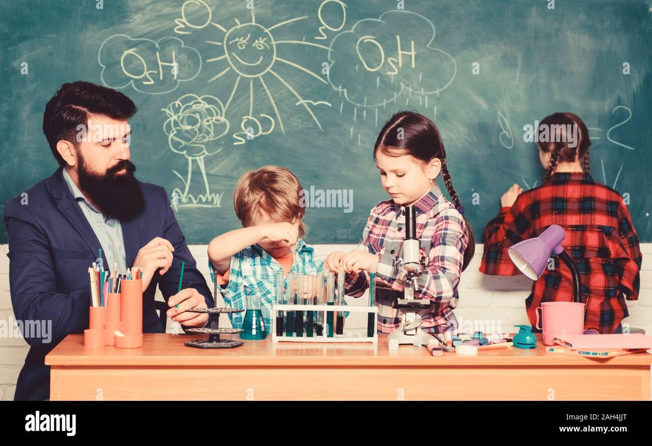 La ciencia es siempre la solución. Experimento de química escolar. Explicando la química para niños. Fascinante lección de química. El hombre barbado profesor y alumnos con tubos de ensayo en el aula. Observe la reacción. Foto de stock