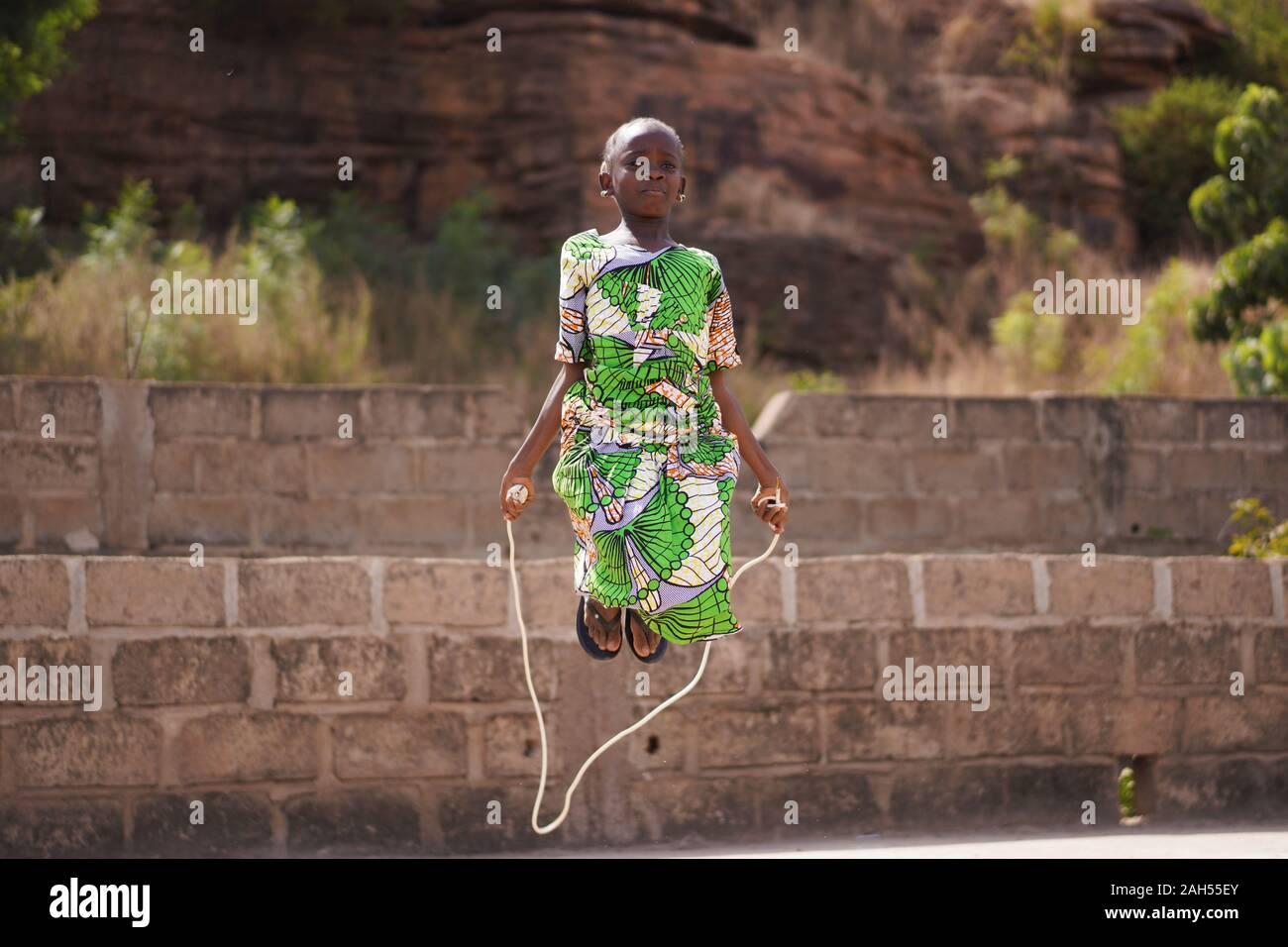 Pequeña muchacha africana con un hermoso vestido verde concentrándose en su omitiendo el rendimiento Foto de stock