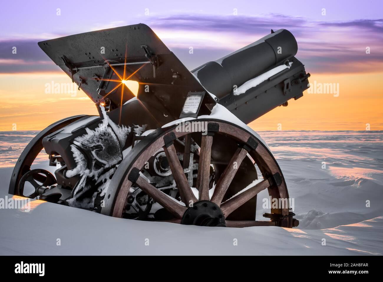 Cerca de un cañón de la primera Guerra Mundial en un monumento conmemorativo de la cima de la montaña cubierto de nieve al amanecer Foto de stock