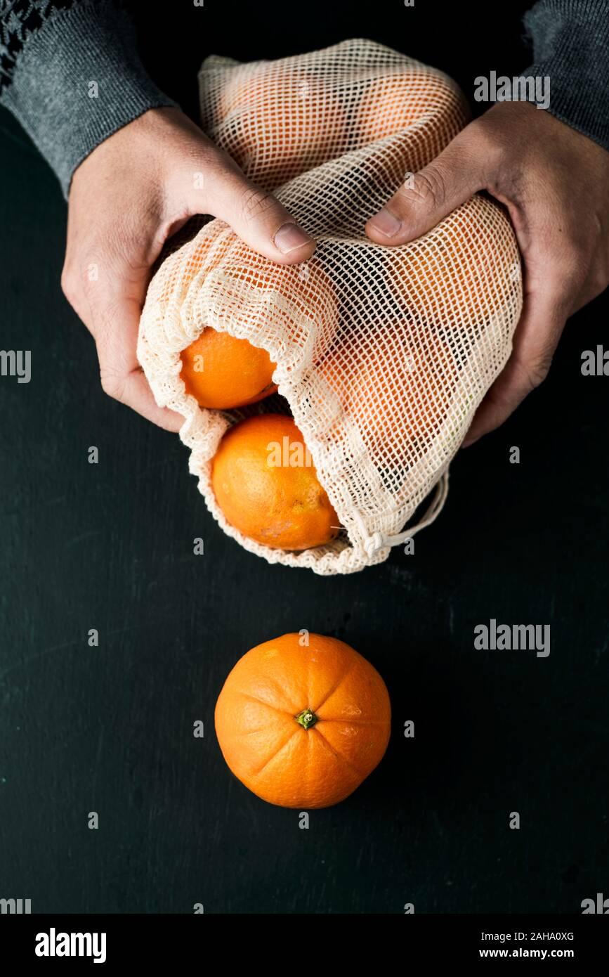 Primer plano de un hombre sujetando una bolsa de malla reutilizables textiles, utilizado para comprar alimentos a granel, lleno de naranjas, como medida para reducir la contaminación plástica Foto de stock