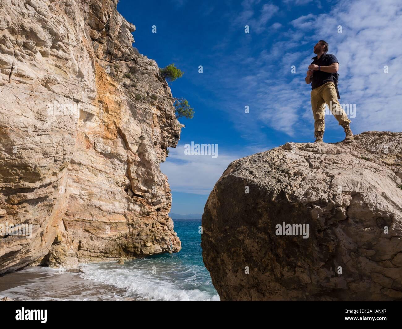 Viajero con mochila en las rocas cerca del mar en busca de distancia. Los viajes de vacaciones de verano. Apuesto joven turista caucásica hombre en ropa casual al aire libre Foto de stock