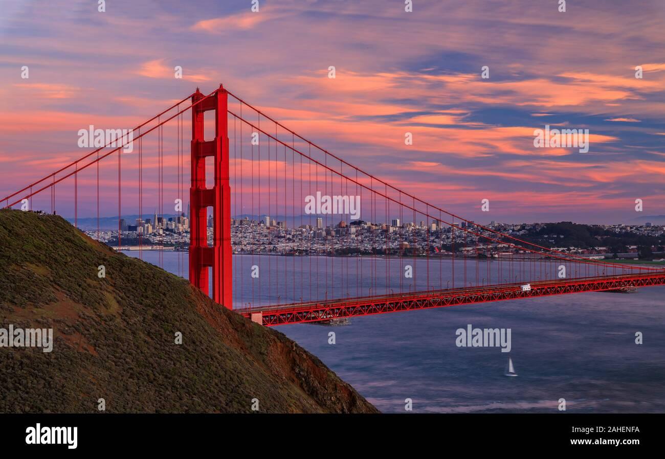 Panorama del puente Golden Gate al atardecer con el Marin en primer plano, el horizonte de San Francisco y las nubes de colores en el fondo Foto de stock