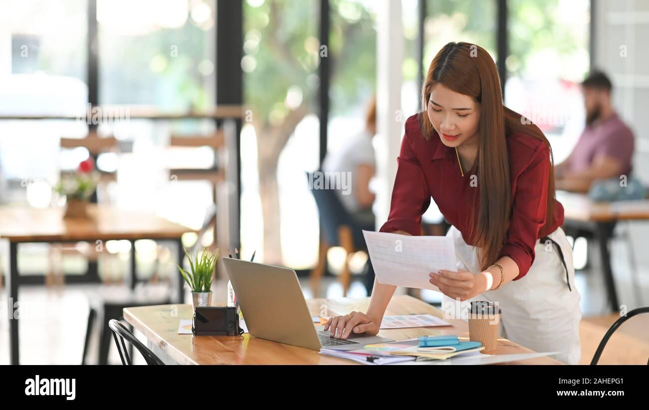 Mujer joven creativo Guía de color seleccionada con el portátil sobre el espacio de trabajo del artista. Foto de stock