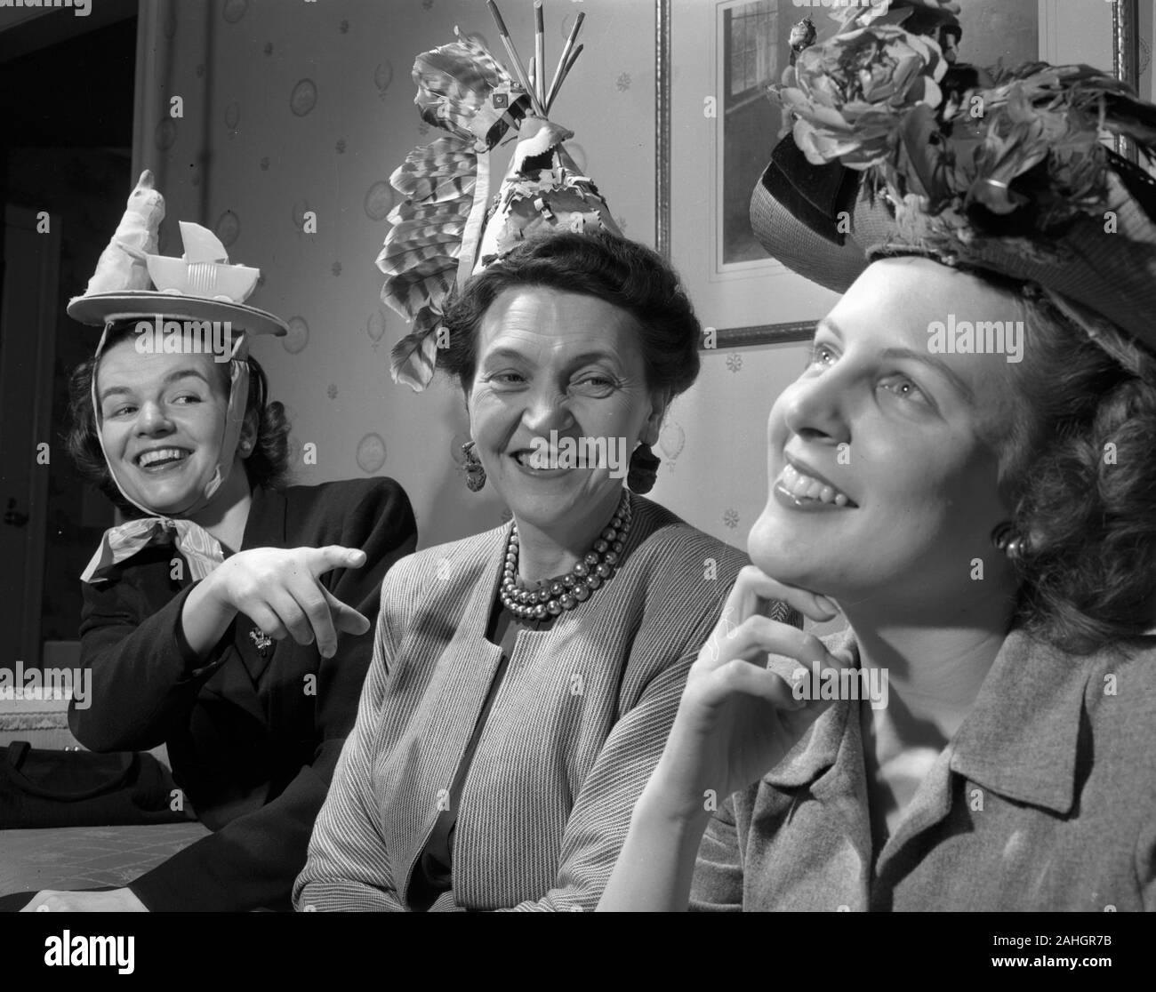Tres mujeres que llevaban varios sombreros divertidos, 1946 Foto de stock