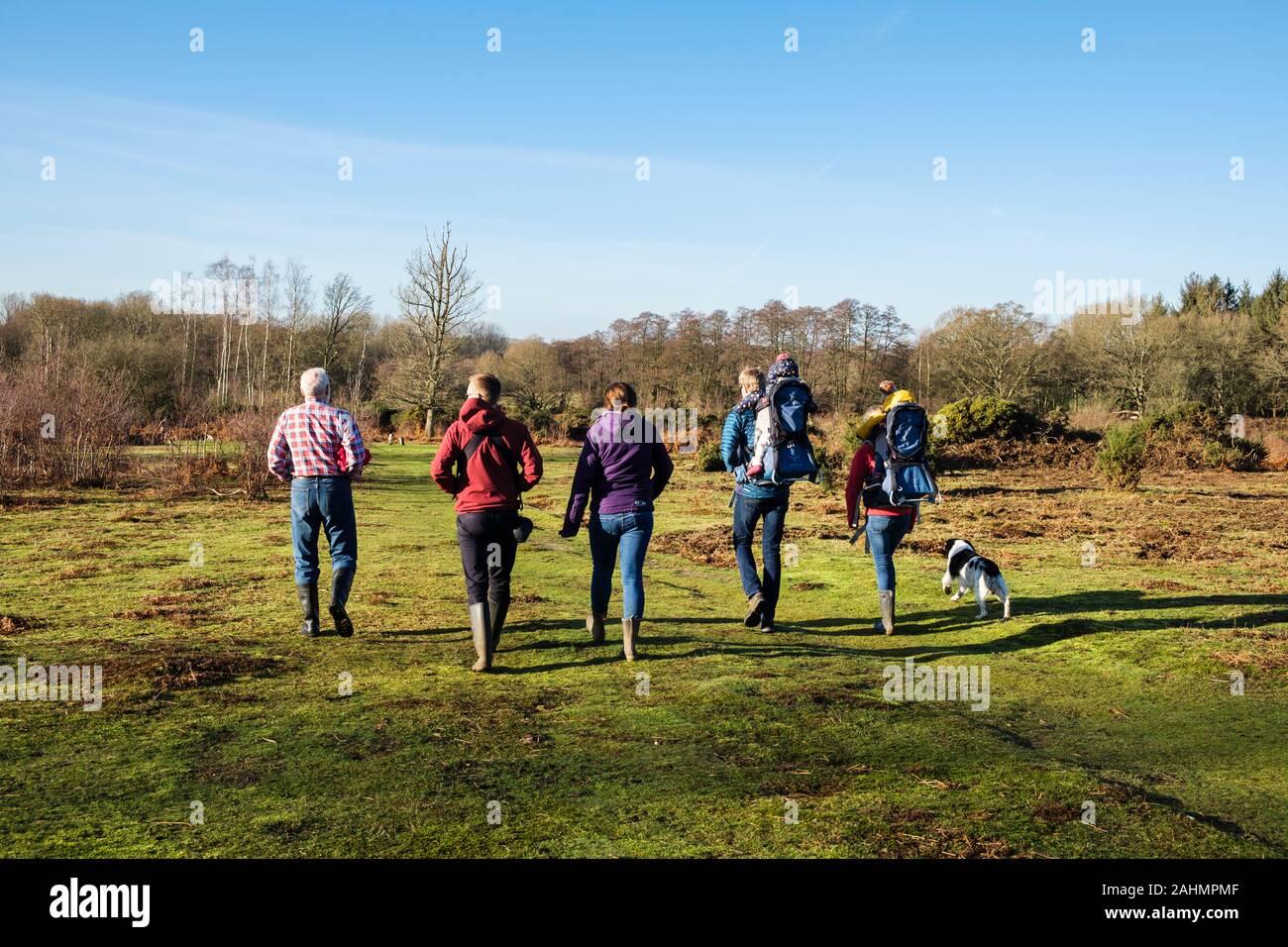 Tres generaciones de una familia caminando con un perro en brezales en Kent Wildlife Trust reserva natural en invierno. Brezales Hothfield Ashford, Inglaterra Foto de stock