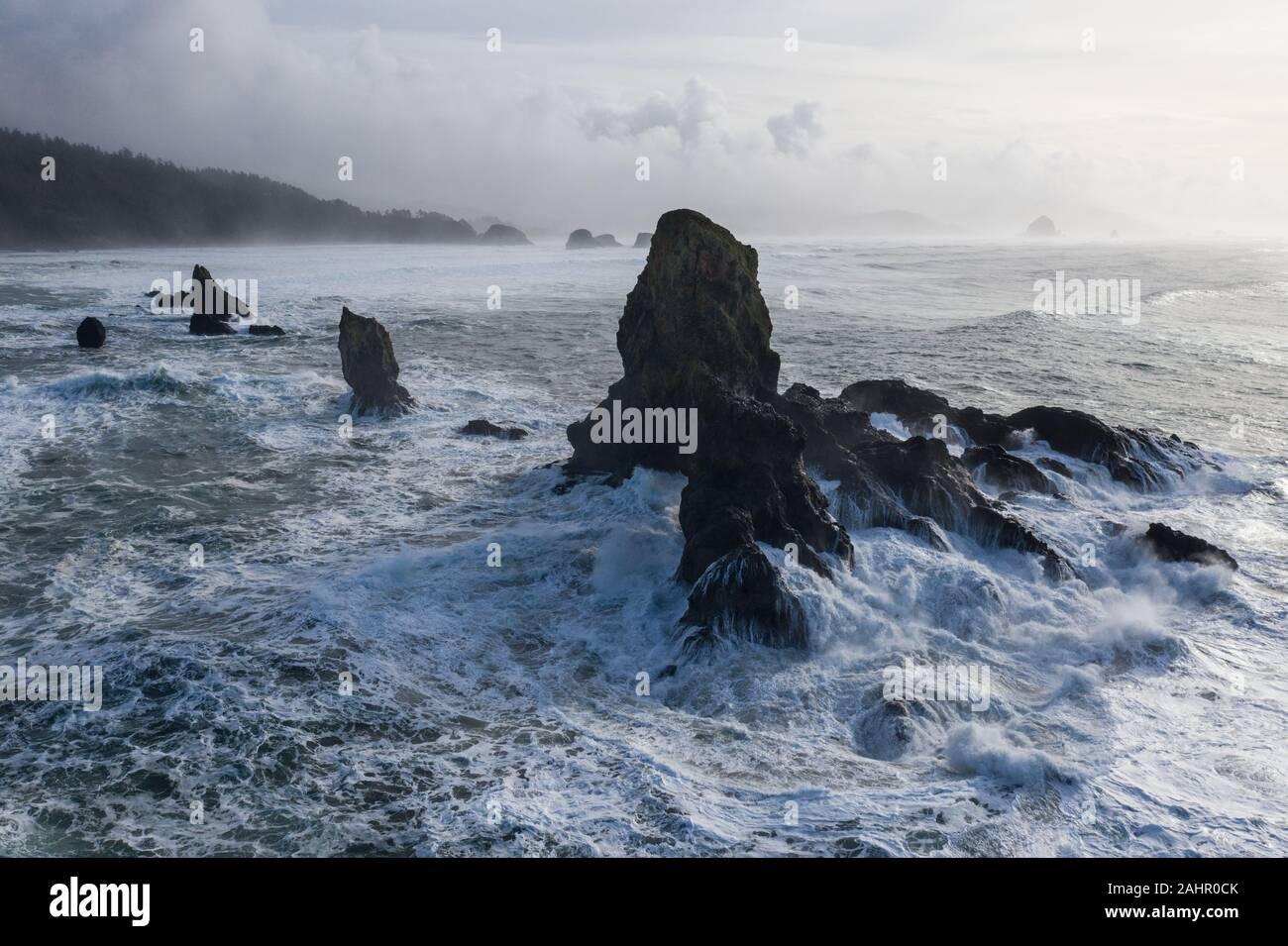 El Océano Pacífico se estrelle contra las rocas de la costa del norte de Oregon. Esta región salvaje, justo al oeste de Portland, es a menudo cubierto por nubes oscuras. Foto de stock