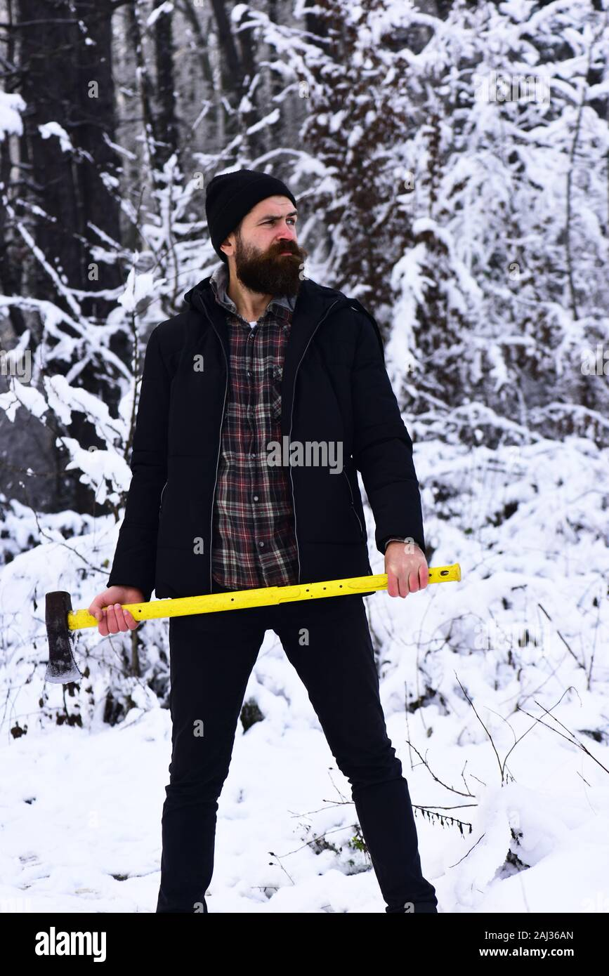 Concepto de senderismo de invierno. El hombre en el sombrero con la barba y el bigote tiene el hacha. Chico con cara pensativa con bosques cubiertos de nieve en el fondo. Forestman con ax amarillo Foto de stock