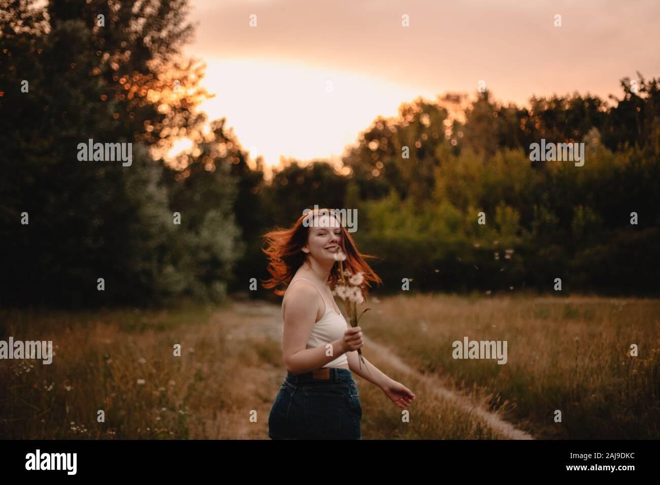 Mujer joven mirando hacia atrás mientras corre en el campo en el bosque en verano Foto de stock