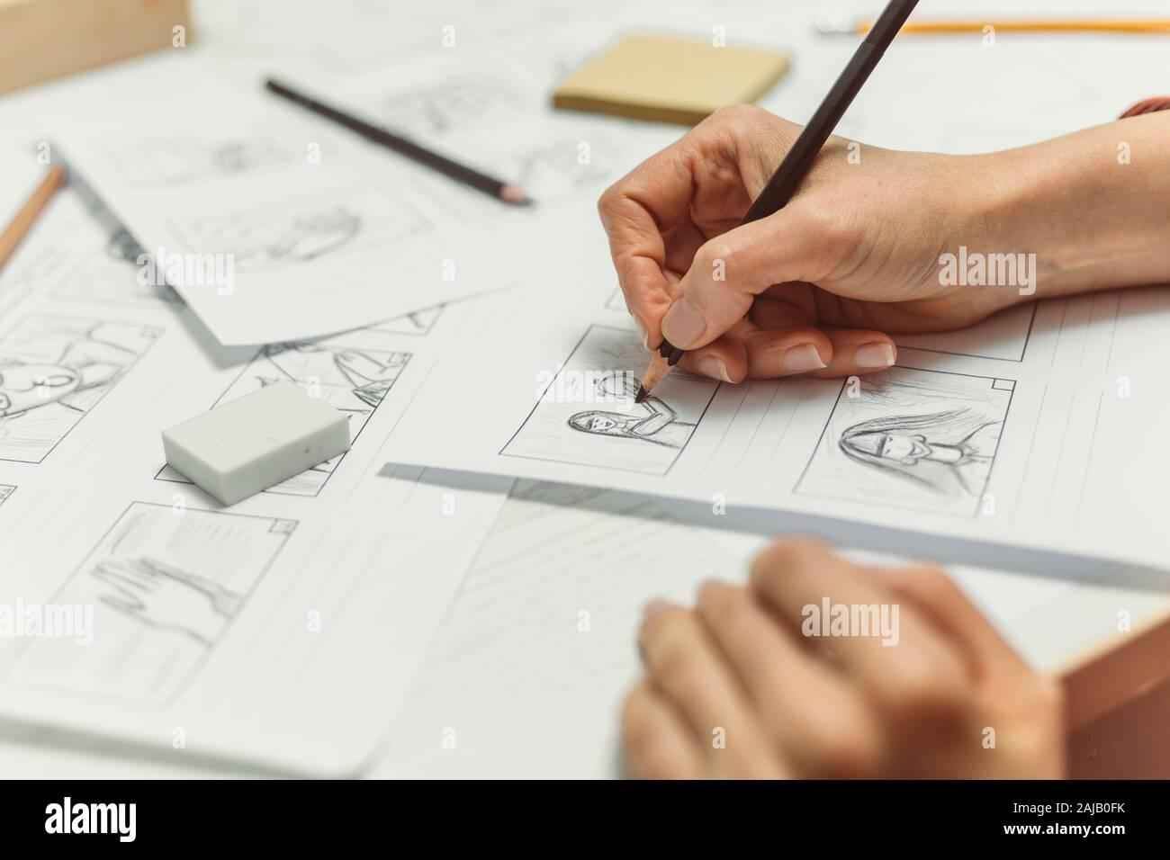 La mano de la mujer dibuja un guión gráfico para una película o una caricatura. Foto de stock