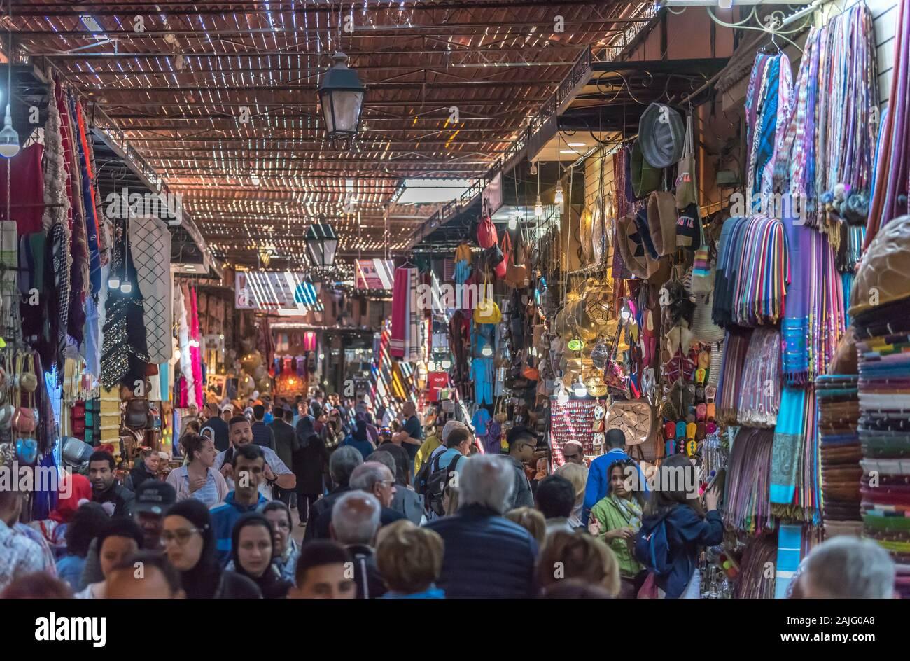 Marrakech, Marruecos: personas y turistas paseando, cabinas y puestos en la callejuela cercana plaza Jemma El Fna, el zoco del mercado dar en la medina de Marrakech, el concurrido bazar Foto de stock