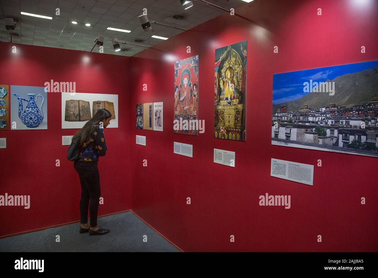 Nueva Delhi, India. El 4 de enero de 2020. (200104) -- Nueva Delhi, 4 de enero de 2020 (Xinhua) -- Un visitante indio mira las fotos en la exposición fotográfica China-India contactos culturales durante la Feria Mundial del Libro de Nueva Delhi-2020 en Nueva Delhi, India, del 4 de enero de 2020. Dentro del pabellón nº 7 en Pragati Maidan, un vasto terreno lugar diseñado para exposiciones, un pabellón enmedio bookstalls en la feria del libro lleva a los visitantes hacia abajo un Memory Lane en más de 2.000 años de intercambios culturales entre China y la India, a través de fotografías. Unos cubículos de distancia desde el pabellón China es la librería llamativamente lucimiento libros chinos en Foto de stock