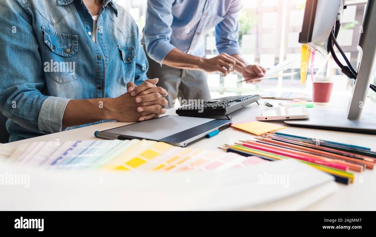 Gráfico creativo arquitecto profesional ocupación desiner escogiendo el color de la paleta pantone muestras para el proyecto de equipo de escritorio de la oficina. Foto de stock