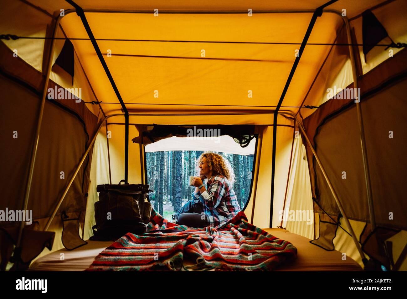 Feliz adulto solitaria mujer caucásica sentarse fuera una carpa disfrutando de una taza de té y la salvaje naturaleza que rodea al aire libre - alternativa libre camping vacatio Foto de stock