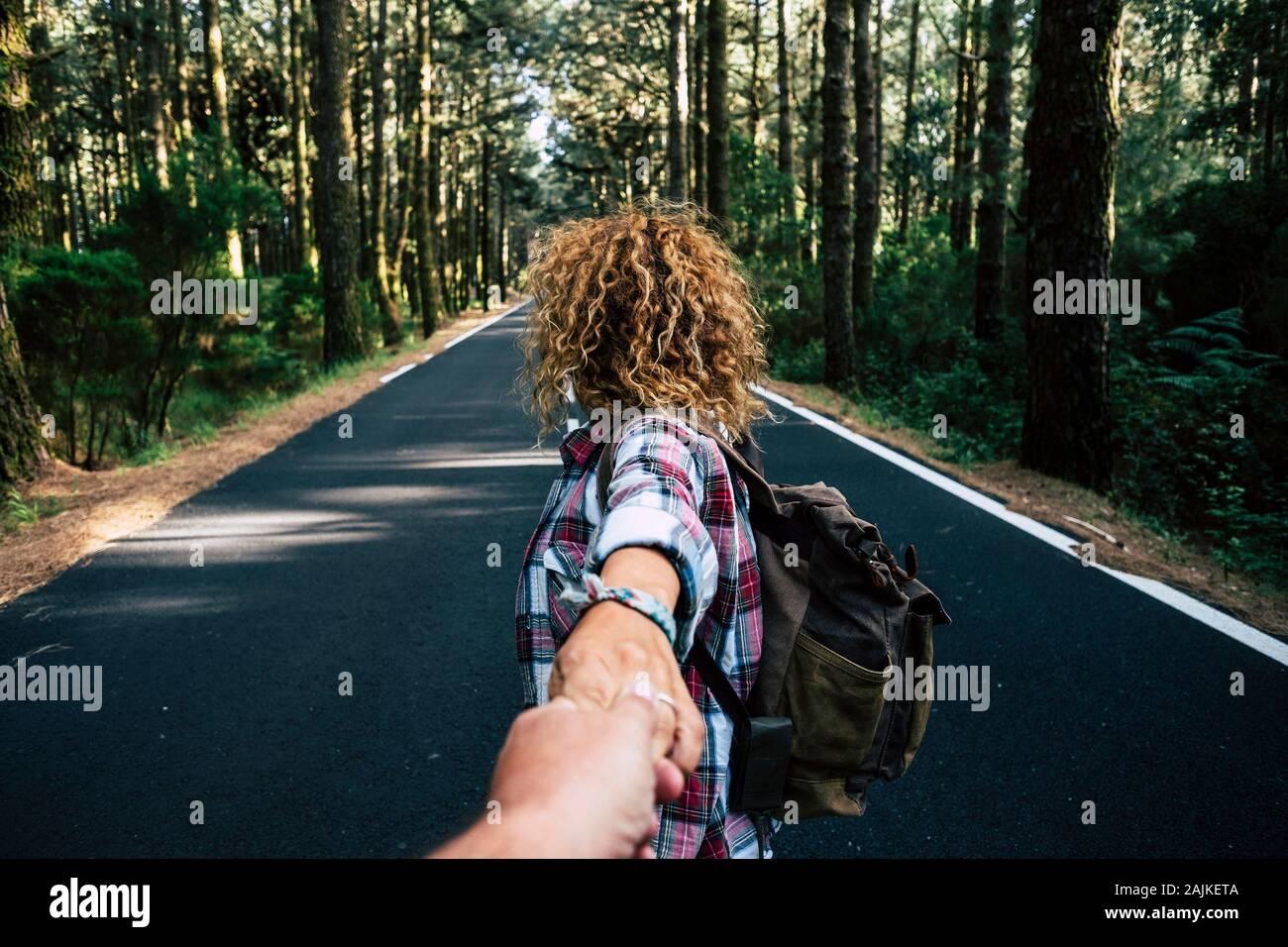 Par viajar juntos caminando con mochila de un bosque en una larga carretera de asfalto - el hombre punto de vista - Manos con amor y relaciones - alte Foto de stock
