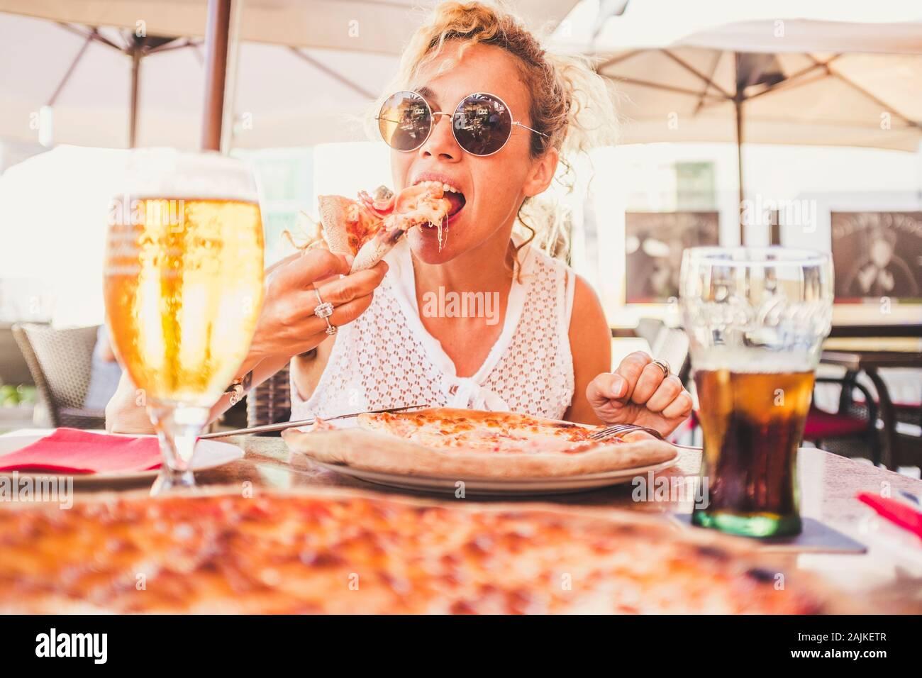 Hermosa mujer caucásica adulta comiendo comida italiana pizze - hombre par punto de vista con cerveza y una bebida fresca en la mesa - gente disfrutando restaura Foto de stock
