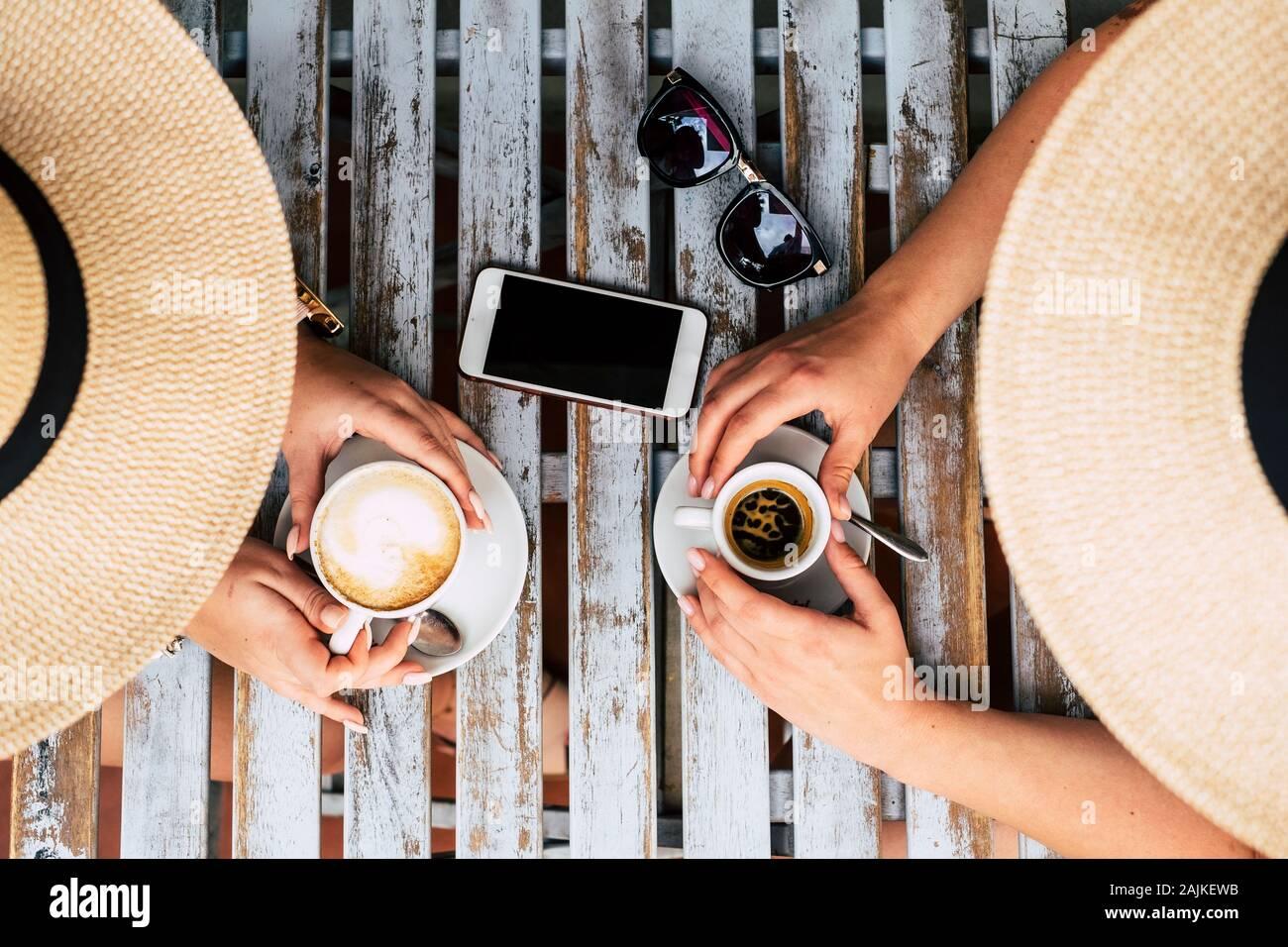 Arriba vetical vista de par del pueblo caucasiano mujeres amigos tomando café y capuchino italiano en el bar - concepto de amistad y al. Foto de stock