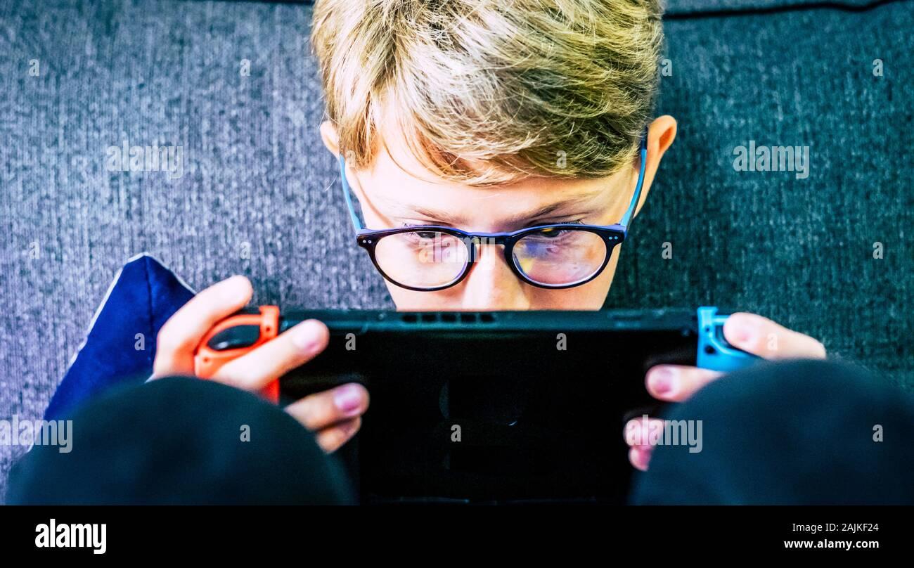 Jóvenes y niños caucásicos concentrado con el dispositivo portátil jugador jugando con tecnología juegos Internet conectado con amigos - video juego adicción Foto de stock