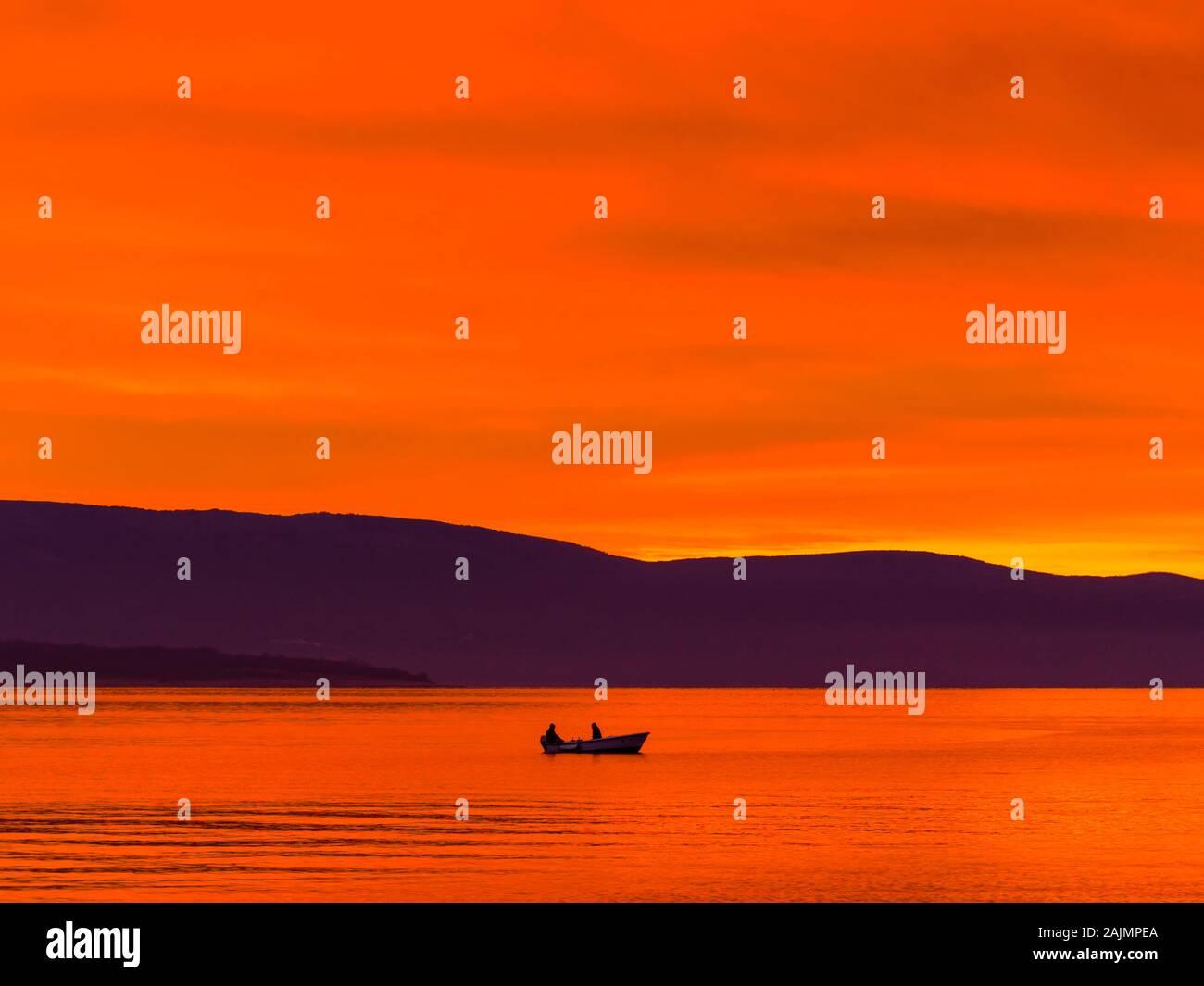 Barco solitario con dos pescadores antes de la gloriosa puesta de sol del mar paisaje panorama Foto de stock
