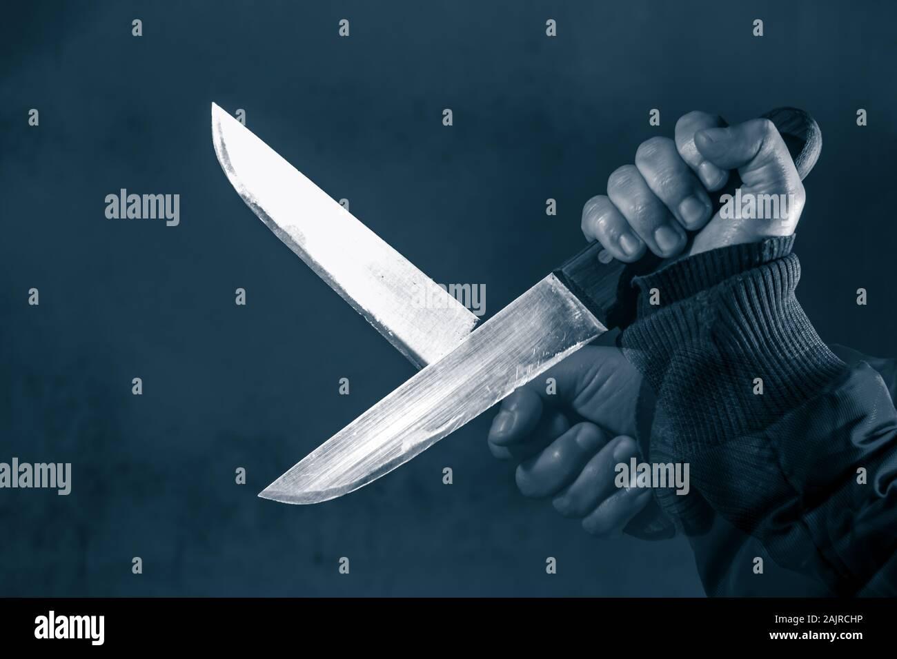 Imagen de tono azul frío compuesto de manos con cuchilla de miedo Foto de stock