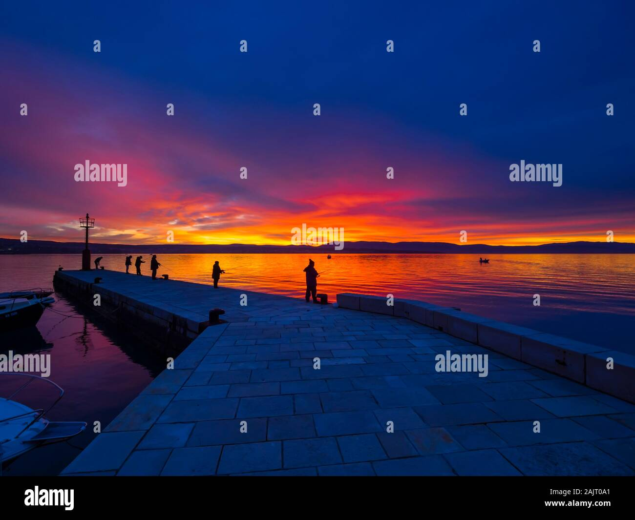 Los pescadores antes del atardecer paisaje en pequeño y tranquilo puerto en Malinska en Croacia Foto de stock