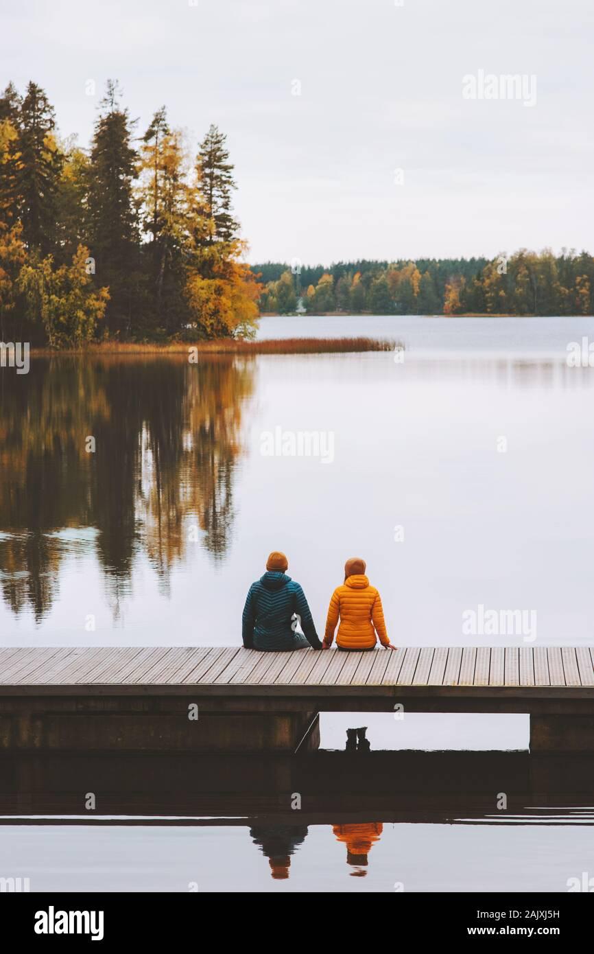Par viajar en Finlandia la vida familiar relación de amor al hombre y a la mujer amigos sentado en el muelle exterior y lago paisaje forestal temporada de otoño Foto de stock