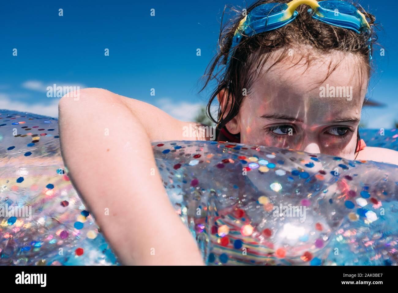 primer plano de una chica triste que parece flotar en la piscina con gafas en la cabeza Foto de stock