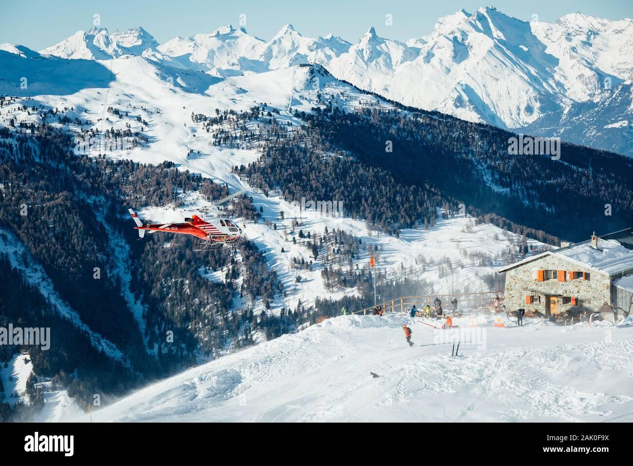 St Luc, Suiza - 30 de diciembre de 2019: rescate de montaña suizo helicóptero despegaba después de recoger heridos esquiador en una estación de esquí de los Alpes Suizos. Foto de stock