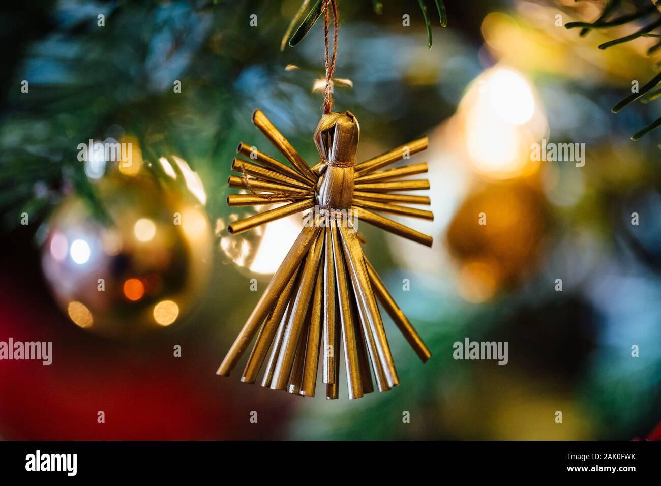 Ángel de paja contra fuera de foco iluminado árbol de navidad. Foto de stock
