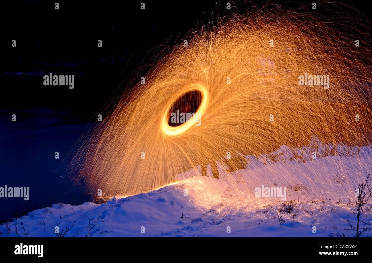 La quema de fuegos artificiales de lana de acero hilado junto a un lago Foto de stock