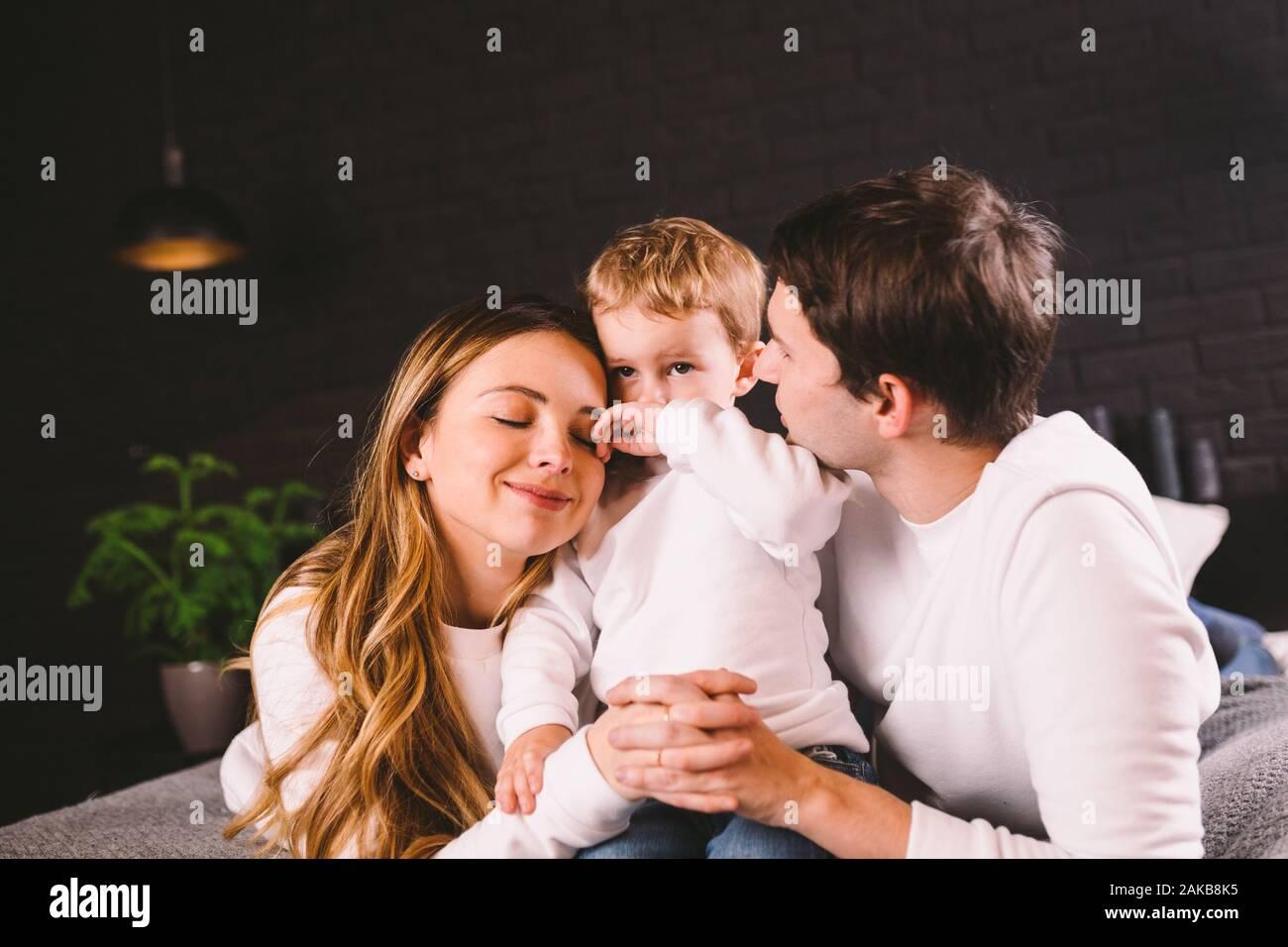 Feliz familia divirtiéndose acostada en la cama, en su casa. Familia feliz en la cama. Papá, mamá e hijo residen en dormitorio en puertas. padre, madre y niño Foto de stock