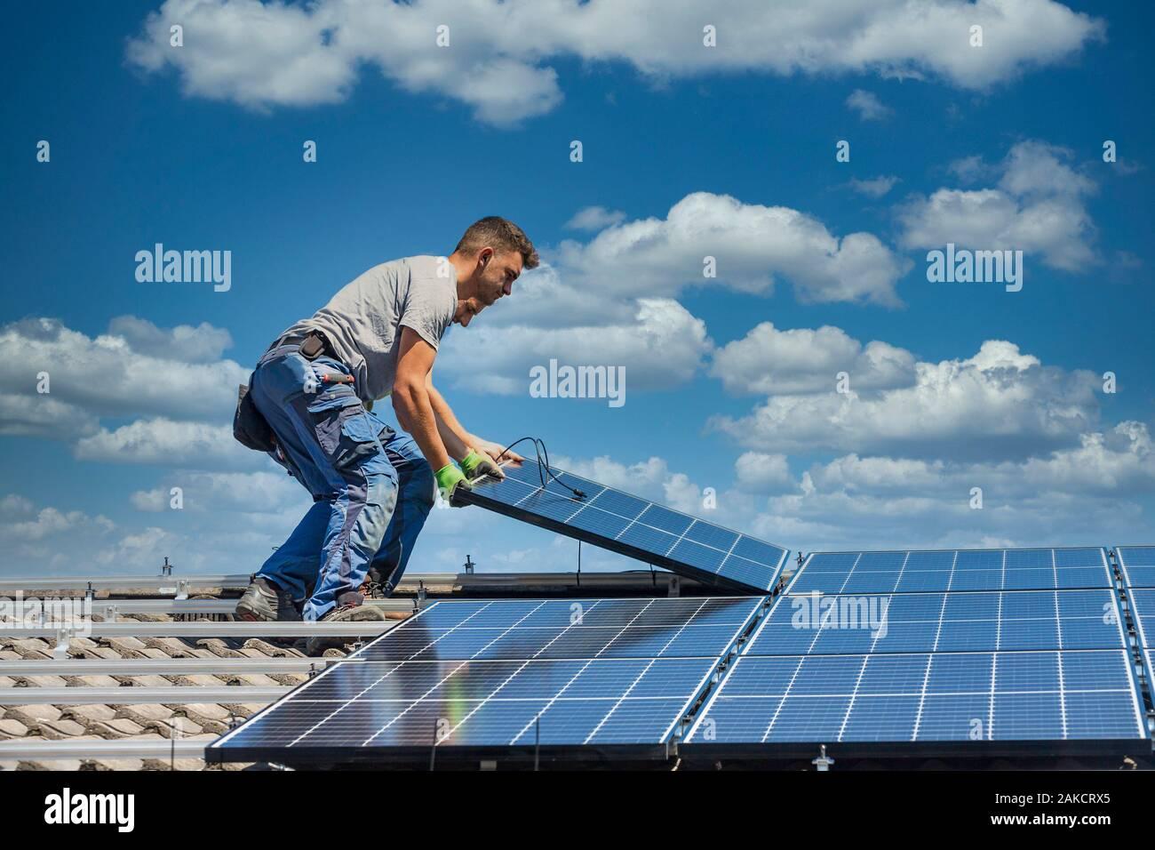 Instalación de sistema de panel solar fotovoltaica. Técnico de panel solar la instalación de paneles solares en el techo. Concepto ecológico de energía alternativa. Foto de stock
