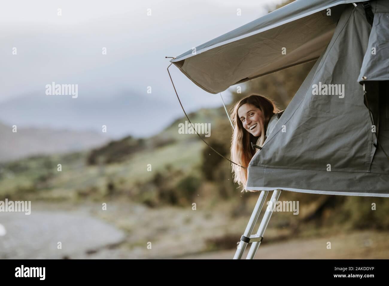 Una joven mujer sonriente se pega la cabeza de una tienda de campaña en Nueva Zelanda. Foto de stock